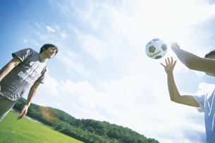 公園でサッカーをする男性2人の写真素材 [FYI02063909]