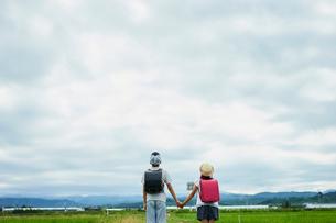 手をつなぐ小学生の兄妹と空の写真素材 [FYI02063918]