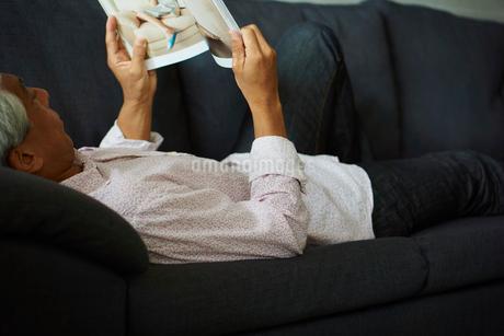 ソファに寝転び本を読むシニア男性の写真素材 [FYI02064023]