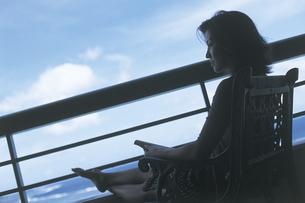 海とテラスの女性シルエットの写真素材 [FYI02064024]