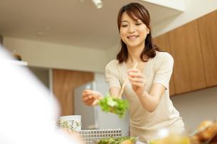 サラダを取り分ける女性の写真素材 [FYI02064070]