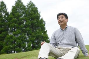 芝生に座るシニア男性の写真素材 [FYI02064121]