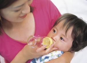 赤ちゃんにミルクを飲ませる母親の写真素材 [FYI02064131]