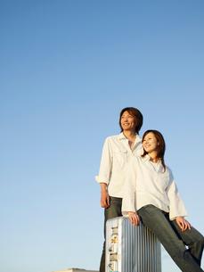 スーツケースとカップルと空の写真素材 [FYI02064157]