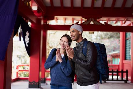 神社で手を合わせる外国人カップルの写真素材 [FYI02064170]