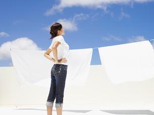 屋上に洗濯物を干す女性の写真素材 [FYI02064180]