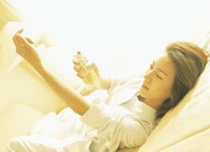横になり手にコロンをつける女性の写真素材 [FYI02064221]
