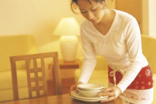 食器を運ぶ女性の写真素材 [FYI02064291]