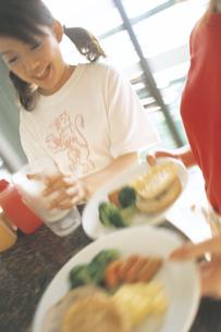 料理をテーブルにのせる女性の写真素材 [FYI02064397]