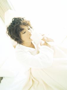 ベッドでコーヒーを飲む女性の写真素材 [FYI02064469]
