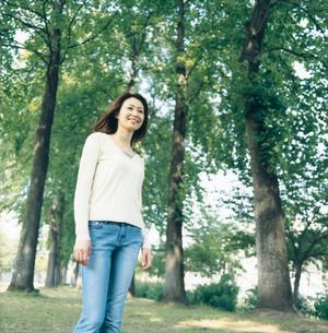 緑の木々とジーンズの女性の写真素材 [FYI02064480]