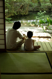 縁側で庭を眺める父親と男の子の写真素材 [FYI02064492]