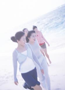 砂浜を歩く女性4人の写真素材 [FYI02064537]