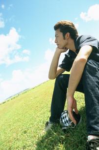 芝生に座る男性の写真素材 [FYI02064606]