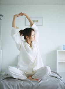 ベッドの上で伸びをするパジャマ姿の女性の写真素材 [FYI02064679]