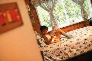 ベッドで本を読む男の子の写真素材 [FYI02064683]