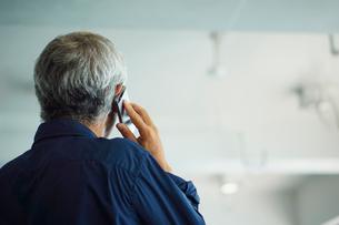 スマートフォンで話すシニア男性の写真素材 [FYI02064699]
