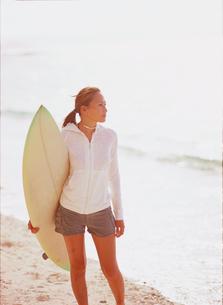 砂浜でサーフボードを抱える女性の写真素材 [FYI02064724]