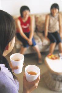 ドリンクを運ぶ女の子とソファに座る女の子2人の写真素材 [FYI02064727]