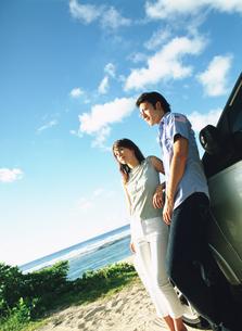 砂浜に止めた車の前に立つカップルの写真素材 [FYI02064777]