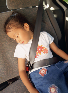 車の中で眠る女の子の写真素材 [FYI02064827]