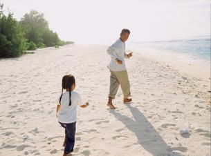 砂浜を走る父親と女の子の写真素材 [FYI02064838]