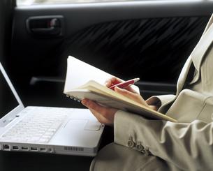車内でノートパソコンとノートを開く女性の写真素材 [FYI02064855]
