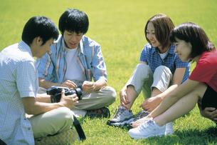 芝生に座る若者達4人の写真素材 [FYI02064856]