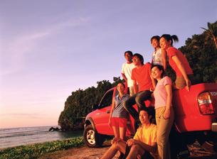 浜辺に止めた赤い車と若者7人の写真素材 [FYI02064861]
