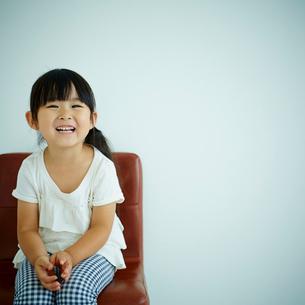 椅子に座る笑顔の女の子の写真素材 [FYI02064903]