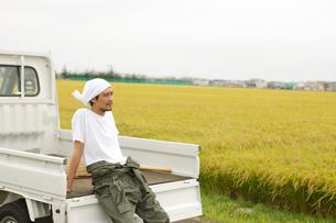 秋の田園で軽トラックに座る男性の写真素材 [FYI02064912]