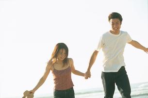 砂浜を手を繋いで歩くカップルの写真素材 [FYI02064919]