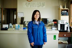 受付カウンターの前に立つ作業着姿の女性の写真素材 [FYI02064932]
