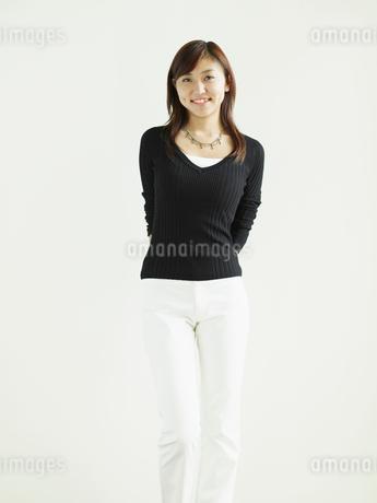 白い壁の前に立つ若い女性の写真素材 [FYI02065013]
