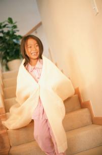 タオルを肩にかけて階段を下りる女の子の写真素材 [FYI02065052]