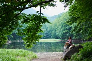 水辺の岩の上に座る女性の写真素材 [FYI02065120]
