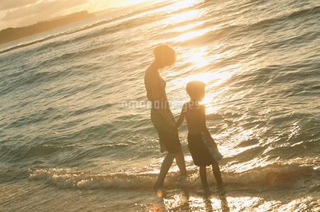 夕暮の波打ち際の母親と子供の写真素材 [FYI02065187]