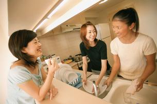 食器を洗う女性2人とコーヒーを飲む女性の写真素材 [FYI02065189]