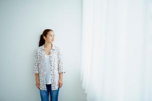 若い女性と窓のカーテンの写真素材 [FYI02065217]
