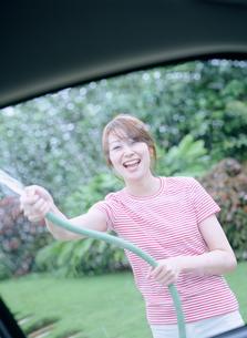 車に水をかける女性の写真素材 [FYI02065233]
