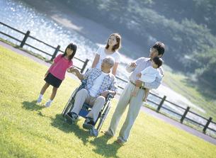 公園で車椅子のシニア男性を囲む家族の写真素材 [FYI02065300]