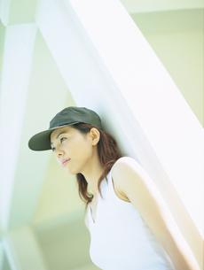 キャップをかぶり壁にもたれる女性の写真素材 [FYI02065310]