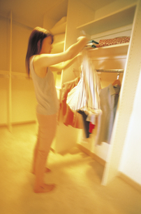 クローゼットの洋服を選ぶ女性の写真素材 [FYI02065347]