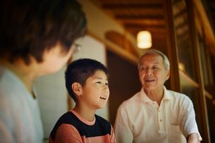 縁側で談笑する祖父母と孫の写真素材 [FYI02065406]