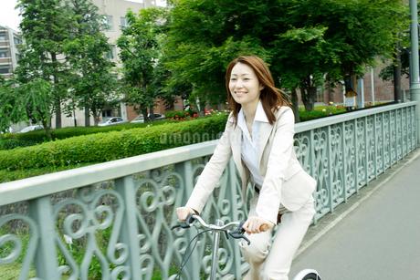 自転車に乗るビジネス女性の写真素材 [FYI02065444]