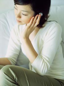 耳に手をあてる女性の写真素材 [FYI02065458]