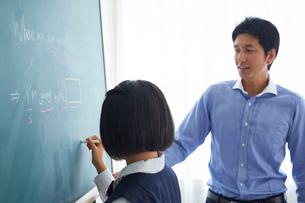 板書する女子中学生と教師の写真素材 [FYI02065460]