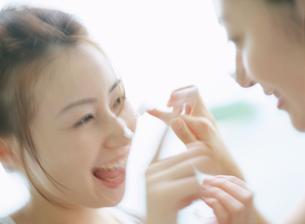 顔にクリームを塗る女性2人の写真素材 [FYI02065474]