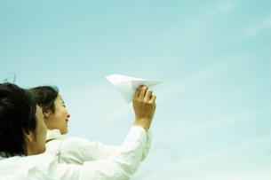 紙飛行機を飛ばす女の子と父親の写真素材 [FYI02065483]