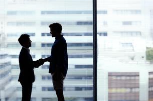 握手をする日本人ビジネスマンと外国人男性の写真素材 [FYI02065499]